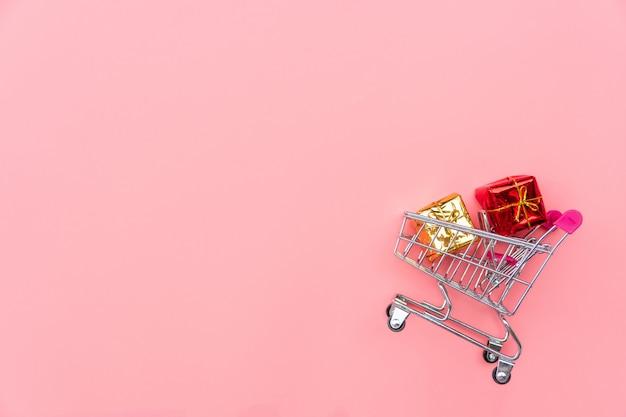 Winkelwagen met geschenkdozen op roze achtergrond. winkelen, winkelen online concept, kopie ruimte, bovenaanzicht