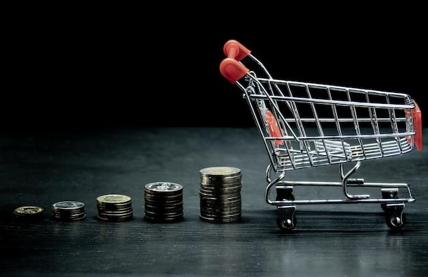 Winkelwagen met groei grafiek van stapel munten