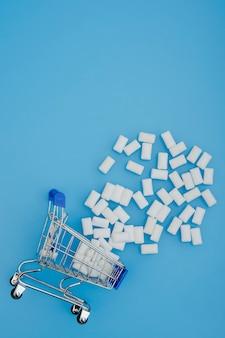 Winkelwagen met kauwgom. creatief idee voor tandheelkunde, gezondheidstanden en bedrijfsconcept. plat leggen.