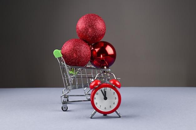 Winkelwagen met kerstballen en een klok