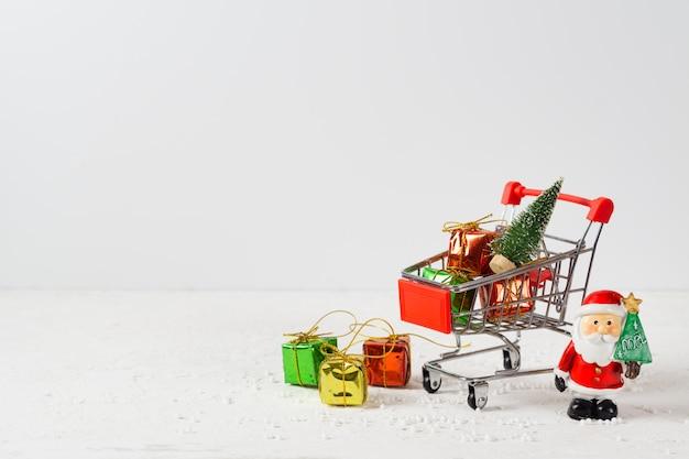 Winkelwagen met kerstboom en miniatuur geschenkdozen en de kerstman