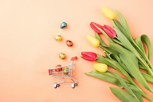 Winkelwagen met kleurrijk boeket tulpen op oranje achtergrond