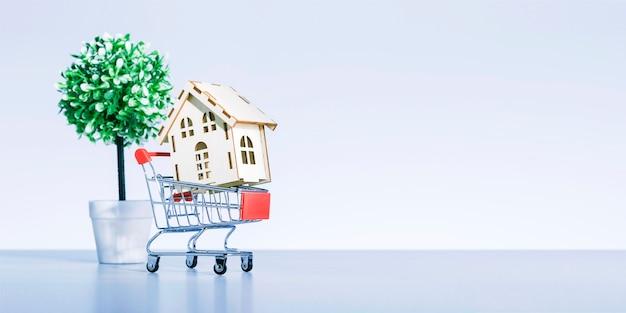 Winkelwagen met model van huis in de buurt van grijze achtergrond met kopie ruimte. vastgoed kopen of verkopen. banier.