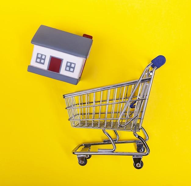 Winkelwagen met rubberen huisjes op een geel