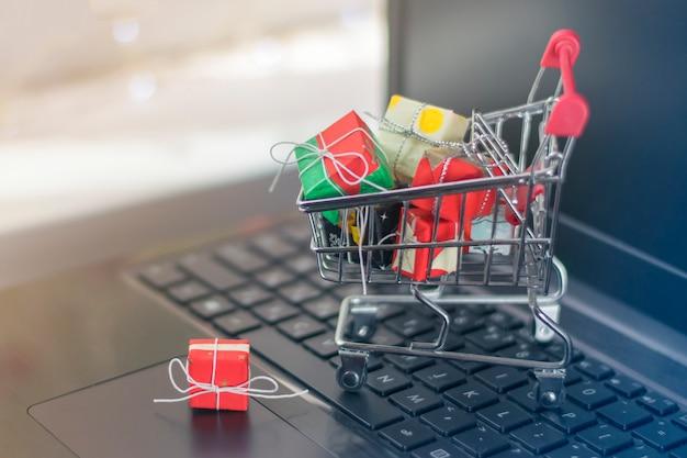 Winkelwagen met verschillende geschenken op het toetsenbord van de laptop. online winkelen concept.