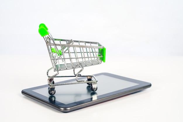 Winkelwagen of metalen trolley op mobiele tablet voor online winkelen en e-commerce.