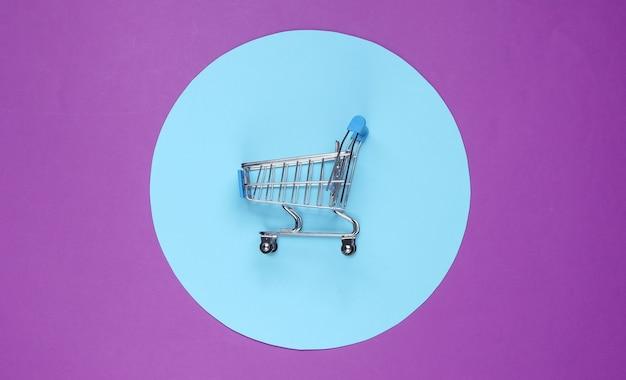 Winkelwagen op paarse achtergrond met blauwe pastel cirkel. minimalistisch winkelconcept, shopaholic.