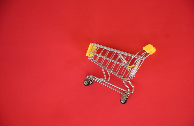 Winkelwagen op rode achtergrond / online winkelen concept met gele winkelwagen op bovenaanzicht - winkelen vakantie