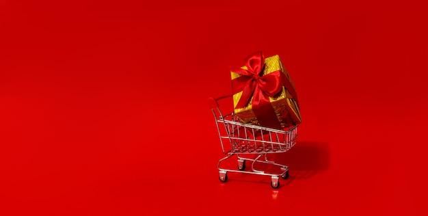 Winkelwagen speelgoed met geschenken in grote doos rode muur. kopieer ruimte. kortingen, verkoop. kerst- en nieuwjaarsuitverkoop.