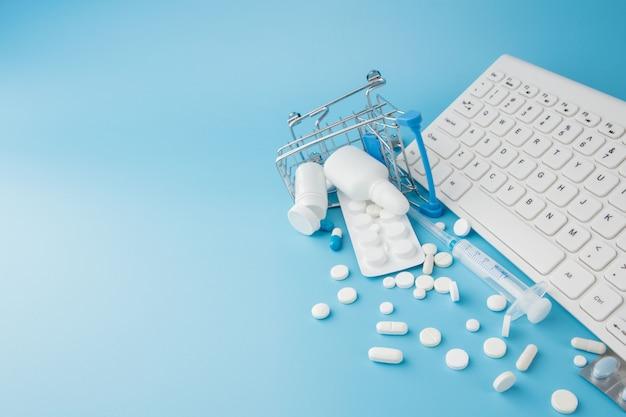 Winkelwagen speelgoed met medicijnen en toetsenbord. pillen, blisterverpakkingen, medische flessen, thermometer, beschermend masker op een blauwe achtergrond. bovenaanzicht met plaats voor uw tekst