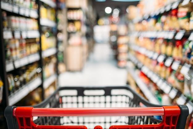 Winkelwagen tussen planken in voedselwinkel
