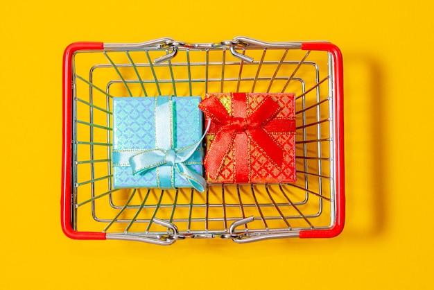 Winkelwagen vol geschenkdozen op een gele achtergrond, bovenaanzicht