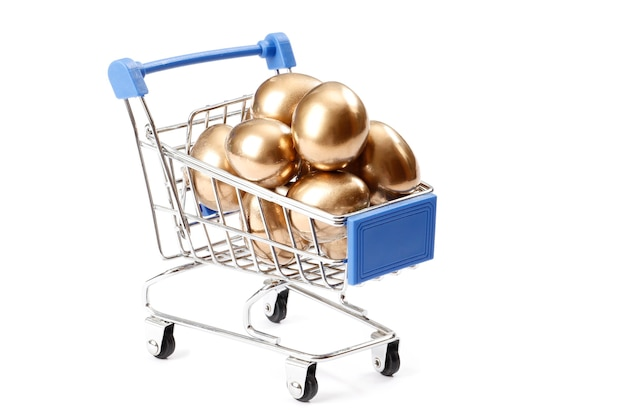 Winkelwagen vol gouden eieren geïsoleerd op witte achtergrond