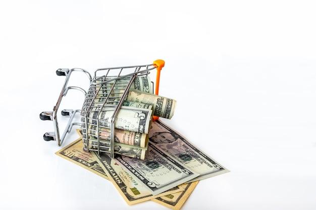 Winkelwagen vol met amerikaanse bankbiljetten op wit wordt geïsoleerd. concept investering