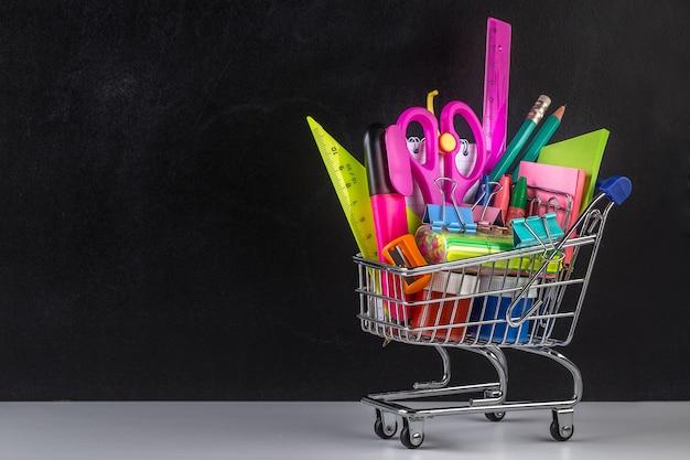 Winkelwagen vol met schoolspullen en een schoolbord