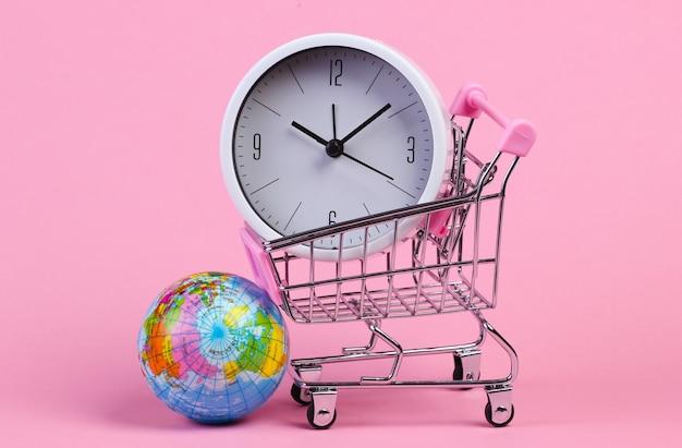 Winkelwagen, wereldbol, klok op roze pastel