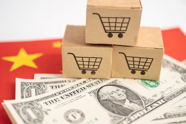 Winkelwagenlogo op doos met amerikaanse dollarbankbiljetten op de vlag van china