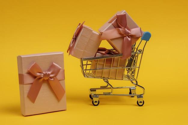 Winkelwagentje en geschenkdozen met bogen op gele achtergrond. samenstelling voor kerst, verjaardag of bruiloft.