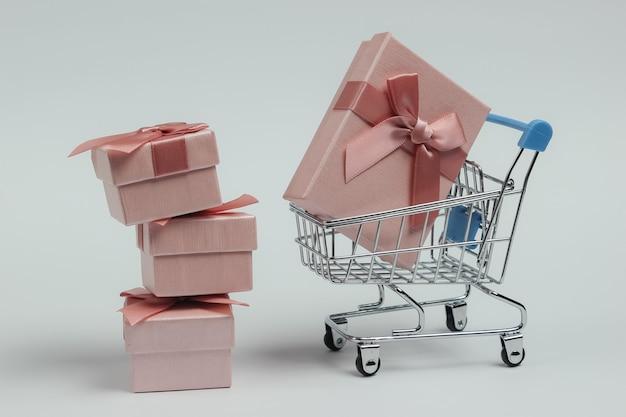Winkelwagentje en geschenkdozen met bogen op witte achtergrond. samenstelling voor kerst, verjaardag of bruiloft.