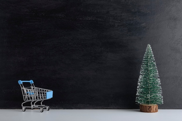 Winkelwagentje en miniatuur kerstboom op zwarte achtergrond. nieuwjaar winkelen. ruimte kopiëren