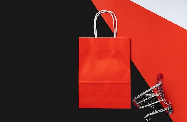 Winkelwagentje en rood pakket op rode en zwarte achtergrond