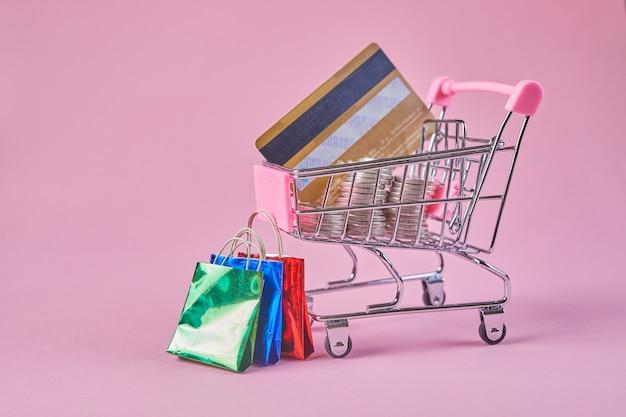 Winkelwagentje met creditcard op een roze achtergrond. creatief idee om online te winkelen.