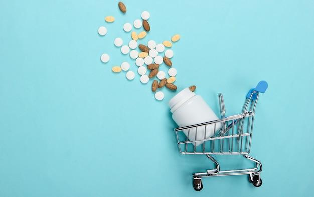 Winkelwagentje met een fles pillen op blauw