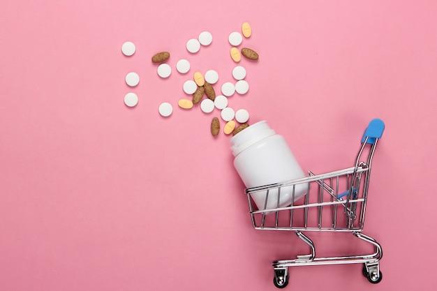 Winkelwagentje met een fles pillen op roze