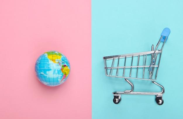Winkelwagentje met een wereldbol op roze en blauwe ondergrond
