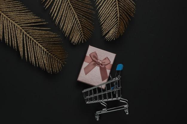 Winkelwagentje met geschenkdoos op zwarte achtergrond met gouden palmbladeren. mode plat lag. zwarte vrijdag. bovenaanzicht