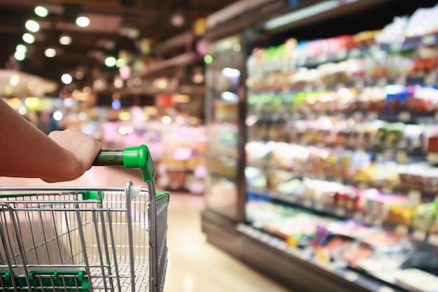 Winkelwagentje met supermarkt achtergrond