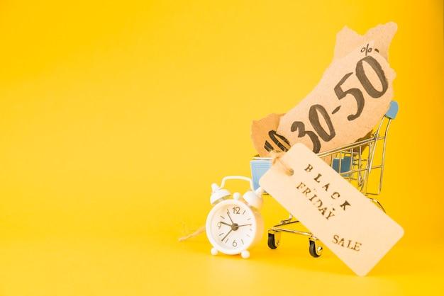 Winkelwagentje met verkoop stukjes papier en tag in de buurt van wekker