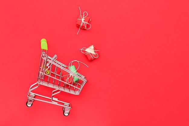 Winkelwagentje op een rode achtergrond met geschenken, bovenaanzicht. kopieer ruimte. bedrijf, verkoopconcept