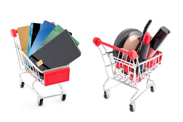 Winkelwagentjes met creditcards en make-upproducten, korting of verkoopthema. must haves en beautyfavorieten op witte achtergrond.