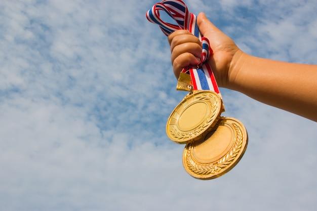 Winnaar hand verhoogd en bezit twee gouden medailles
