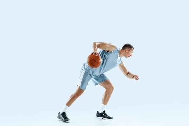 Winnaar. jonge kaukasische basketballer van team in actie, beweging in sprong geïsoleerd op blauwe achtergrond. concept van sport, beweging, energie en dynamische, gezonde levensstijl. trainen, oefenen.
