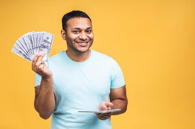 Winnaar! jonge rijke gelukkig afro-amerikaanse indiase zwarte man in casual geld dollarbiljetten met verrassing geïsoleerd over gele muur achtergrond. tablet gebruiken.