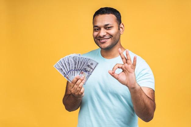 Winnaar! jonge rijke gelukkig afro-amerikaanse indiase zwarte man in casual geld dollarbiljetten met verrassing geïsoleerd over gele muur achtergrond.