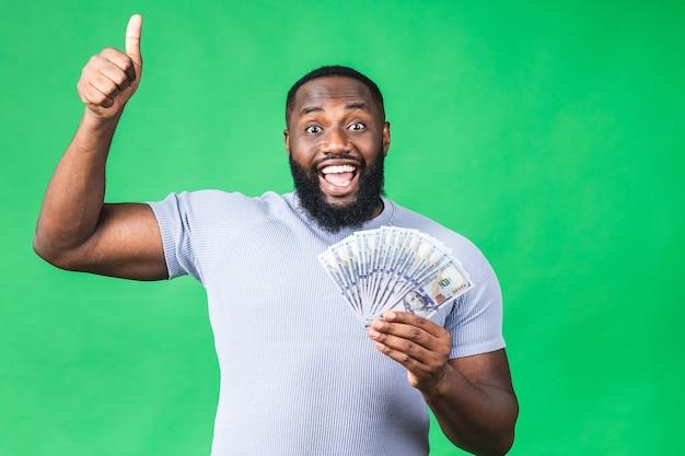 Winnaar! jonge rijke gelukkig afro-amerikaanse man in casual bedrijf geld dollarbiljetten en portemonnee met verrassing geïsoleerd over groene muur achtergrond. duimen omhoog.