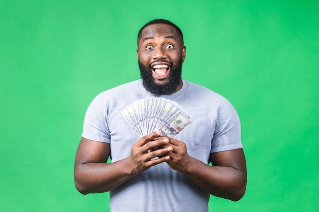 Winnaar! jonge rijke gelukkig afro-amerikaanse zwarte man in casual geld dollarbiljetten en portemonnee met verrassing geïsoleerd over groene muur achtergrond.