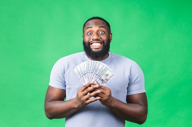 Winnaar! jonge rijke gelukkig afro-amerikaanse zwarte man in casual geld dollarbiljetten met verrassing geïsoleerd over groene muur achtergrond.