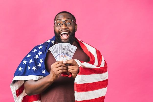 Winnaar! jonge rijke gelukkig afro-amerikaanse zwarte man in casual geld dollarbiljetten met verrassing geïsoleerd over roze achtergrond.