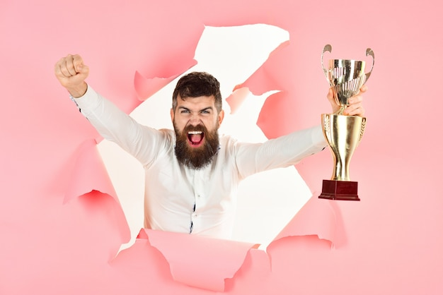 Winnaar opgewonden man kijkt door gat en houdt prijs bebaarde man maakt gat in papieren overwinning