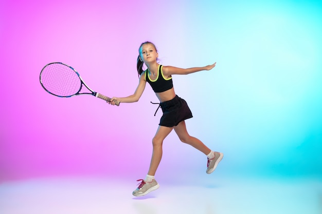 Winnaar. weinig tennismeisje in zwarte sportwear die op gradiënt wordt geïsoleerd