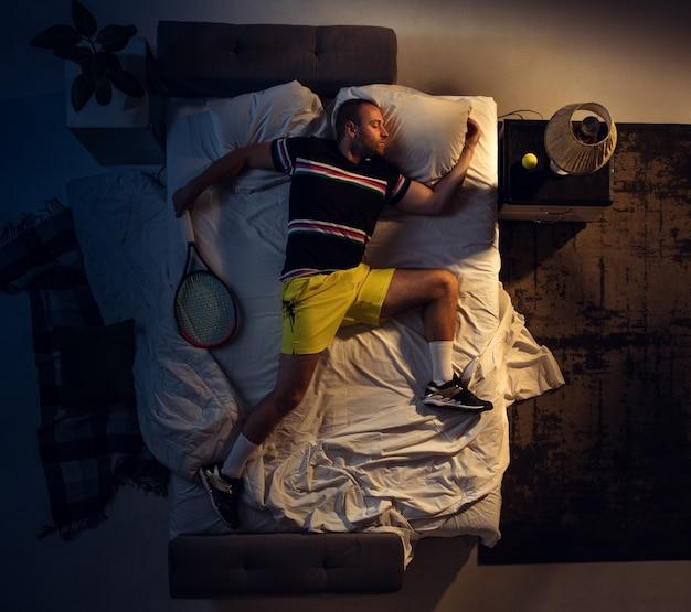 Winnen. bovenaanzicht van jonge professionele tennisser slapen in zijn slaapkamer in sportkleding met racket. hij houdt nog meer van zijn sport dan van comfort, kijken naar een wedstrijd, zelfs als hij rust. actie, beweging, humor.