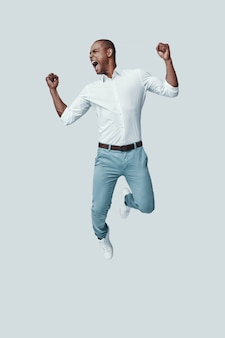 Winnen. knappe jonge afrikaanse man gebaren en schreeuwen terwijl hij tegen een grijze achtergrond zweeft