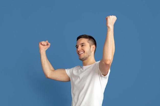 Winnen. portret van de blanke jonge man geïsoleerd op blauwe studio muur. wedden.