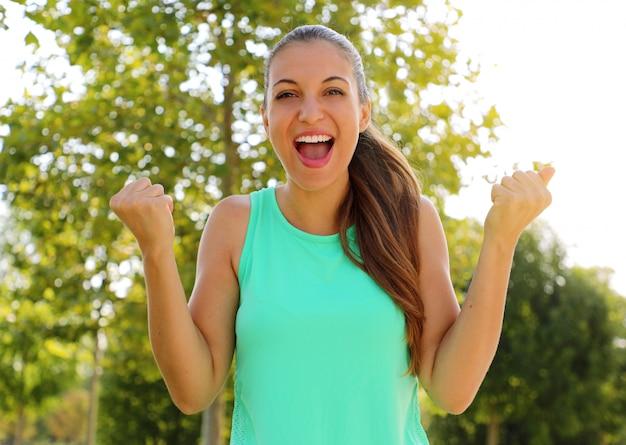Winnen, succesconcept. mooi, sportief fitnessmeisje verheugt zich in de overwinning, heft haar vuisten op als teken van overwinning. positieve emoties en gevoelens.