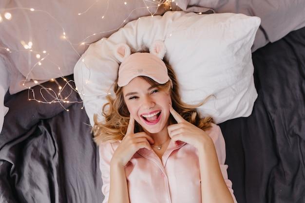 Winnend blond meisje in schattig eyemask plezier vroeg in de ochtend. schitterend krullend vrouwelijk model dat in bed ligt en glimlacht.