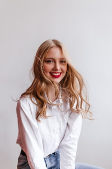Winnend blondemeisje in overhemd met glimlach. gelukkige blanke dame geïsoleerd op lichte muur.